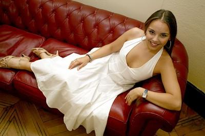Chenoa con un vestido blanco recostada en un sofá rojo