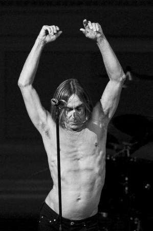 Iggy Pop sin camiseta y con los brazos en alto
